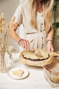 하얀 탁자에 크림을 얹은 맛있는 초콜릿 케이크를 만드는 젊은 여성 제빵사