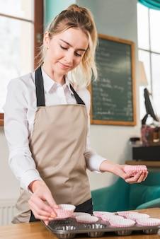 Молодая женщина-пекарь размещает пустые бумажные формы для кексов