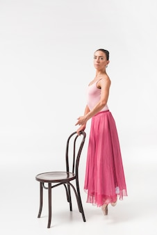 Young female ballerina dancer standing on one leg holding chair against white backdrop