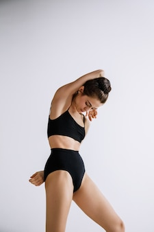 Young female ballet dancer in black bodysuit against white studio wall