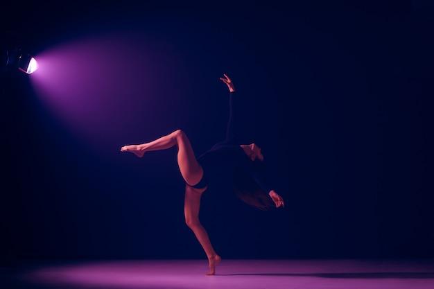 ネオンライトスタジオの背景で踊る若い女性のバレエダンサー。白人モデルのバレリーナプロジェクト。バレエ、ダンス、アート、コンテンポラリー、振り付けのコンセプト