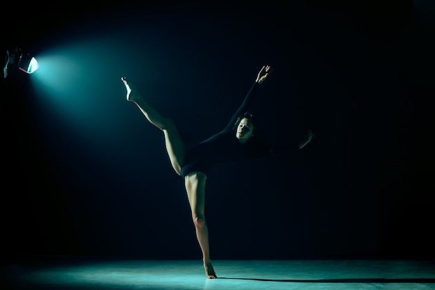 ネオンライトスタジオの背景バレリーナプロジェクトで踊る若い女性のバレエダンサー