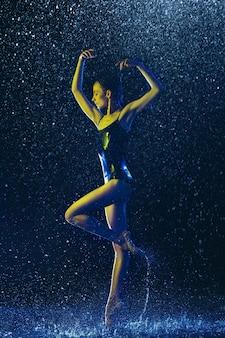 水滴とスプレーの下で演奏する若い女性のバレエダンサー。ネオンの光で踊る白人モデル。魅力的な女性。バレエとコンテンポラリー振り付けのコンセプト。クリエイティブアート写真。