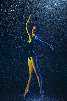 水滴とスプレーの下で実行する若い女性のバレエ ダンサー。ネオンの光で踊る白人モデル。魅力的な女性。バレエとコンテンポラリーダンスのコンセプト。クリエイティブ アート写真。