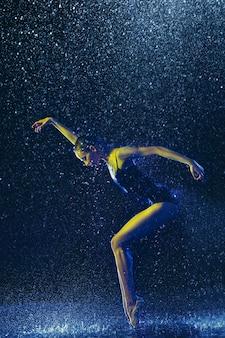 水滴とスプレーの下で演奏する若い女性のバレエダンサー。ネオンの光で踊る白人モデル。魅力的な女性。バレエとコンテンポラリー振り付けのコンセプト。