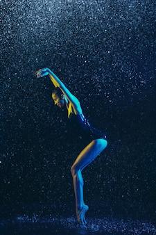 水滴とスプレーの下で演奏する若い女性のバレエダンサー。ネオンの光で踊る白人モデル。魅力的な女性。