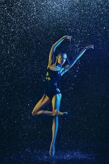Giovane ballerina femminile che esegue sotto gocce d'acqua e spray. modello caucasico ballando in luci al neon. donna attraente. balletto e concetto di coreografia contemporanea. foto di arte creativa.