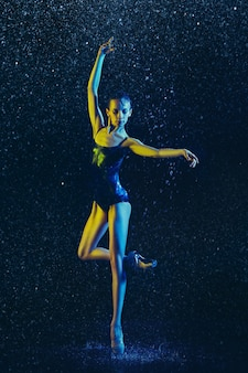 Young female ballet dancer performing under water drops and spray. caucasian model dancing in neon lights. attractive woman. ballet and contemporary choreography concept.