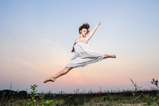 若い女性のバレエダンサーは日没で屋外を実行します
