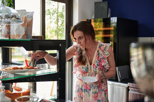 若い女性のバリスタ、起業家はコーヒーハウスのショーケースでデザートを選び、自分のカフェで顧客にサービスを提供するためにそれらを皿に置きます