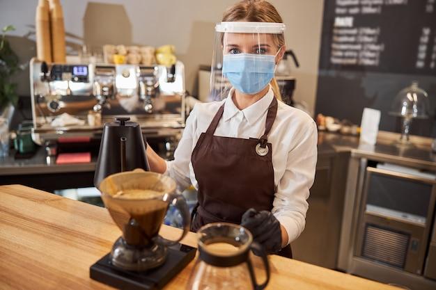 젊은 여성 바리스타가 끓는 물과 필터로 커피를 만들고 있다