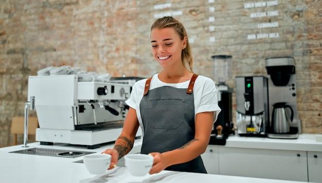 Молодая женщина-бариста стоит у стойки в кофейне и улыбается, подавая клиенту чашки приготовленного кофе.