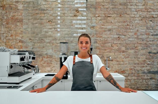 젊은 여성 바리 스타는 커피 숍의 카운터에 서서 미소 짓습니다.