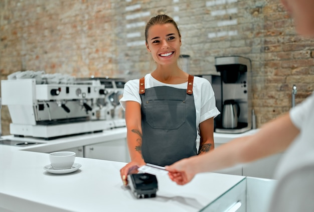 若い女性のバリスタが喫茶店のカウンターに立っています。カフェでクレジットカードで注文の支払いをしている顧客。