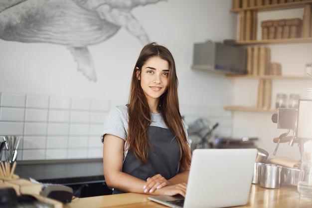 カフェで彼女の仕事でラップトップコンピューターを使用して若い女性バリスタ。カメラの笑顔を見て幸せな従業員。