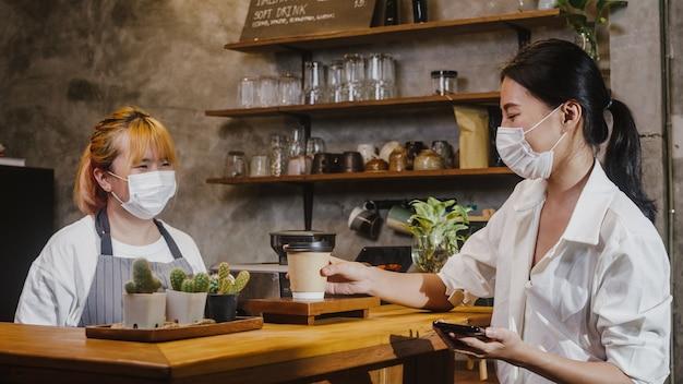 젊은 여성 바리 스타는 카페에서 소비자에게 뜨거운 커피 종이 컵을 가져가는 얼굴 마스크를 착용합니다.