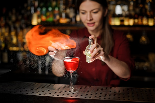 Young female bartender sprinkling a cocktail glass filled with aperol syringe cocktail with a peated whisky and making a smoky note