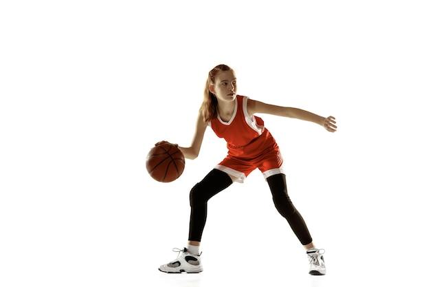 Giovane giocatore di basket femminile in azione, movimento in esecuzione isolato sul muro bianco
