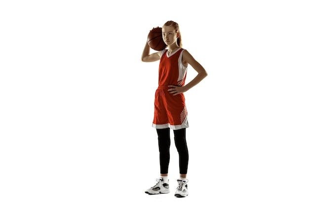Giovane giocatore di pallacanestro femminile in posa sicuro isolato sul muro bianco