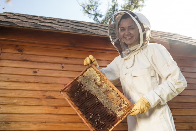 Young female beekeeper hold wooden frame with honeycomb.