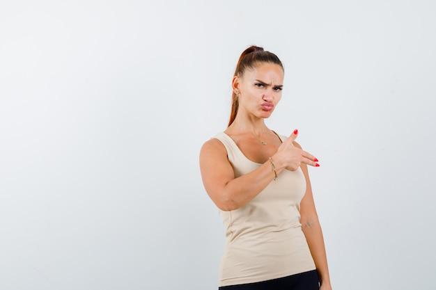 Giovane femmina in canottiera beige che mostra il gesto della pistola e che sembra sicura, vista frontale.