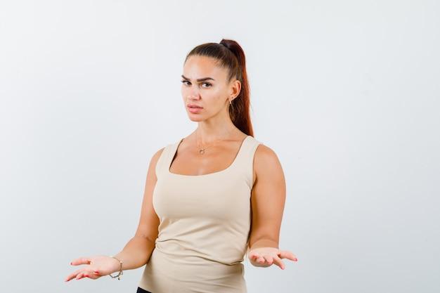 Giovane donna in canottiera beige che allunga le mani nel gesto interrogativo e che sembra seria, vista frontale.