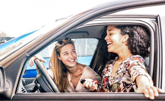 Young female best friends having fun at car roadtrip moment
