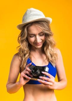 Young female in bikini is considering camera