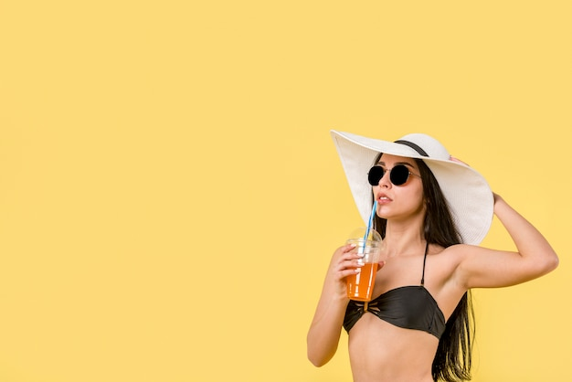 Young female in bikini with cocktail