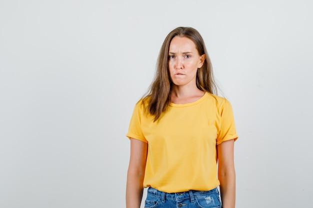 若い女性がtシャツ、ショートパンツで唇を噛み、がっかりしているように見えます。正面図。