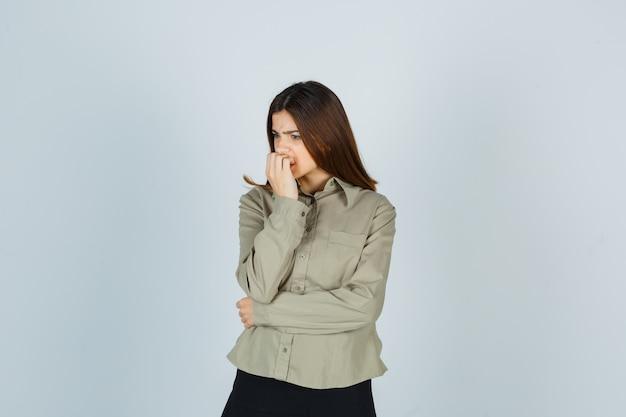 Giovane femmina che morde le unghie emotivamente in camicia, gonna e sembra ansiosa. vista frontale.
