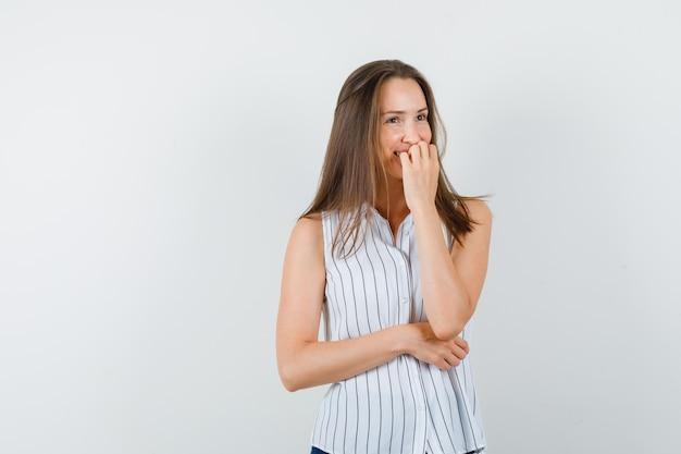 Tシャツ、ジーンズで爪を噛み、陽気に見える若い女性。正面図。