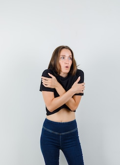 Young female in black blouse, pants hugging herself and feeling cold