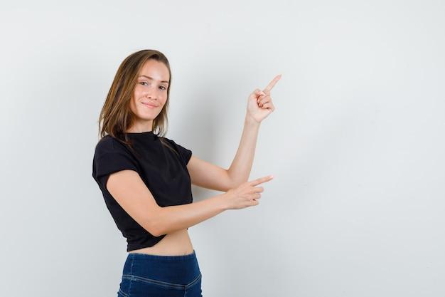 Giovane donna in camicetta nera, pantaloni rivolti verso l'alto e guardando fiducioso