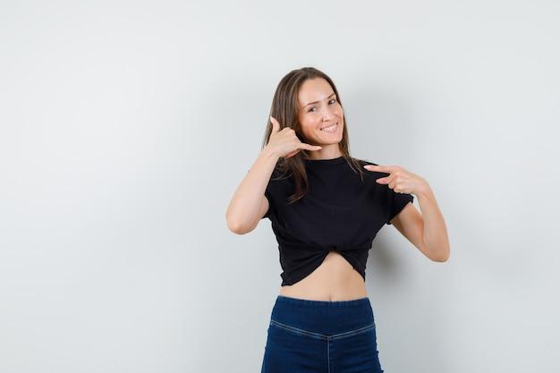 Giovane femmina in camicetta nera, pantaloni che mostrano chiamami gesto e sembra allegra