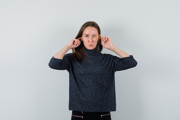 Young female in black blouse plugging ears while winking and looking uncomfortable