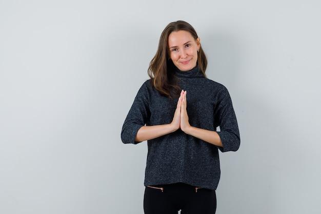 Giovane donna in camicetta nera che mostra il gesto di namaste e sembra felice