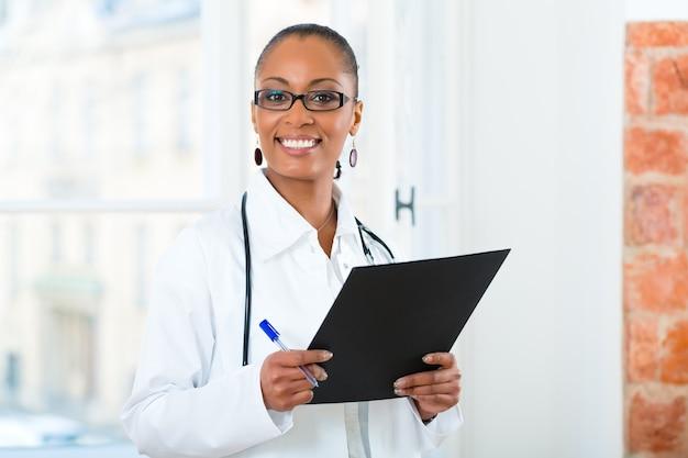 Молодая женщина-черный врач стоит у окна в клинике с файлом или досье