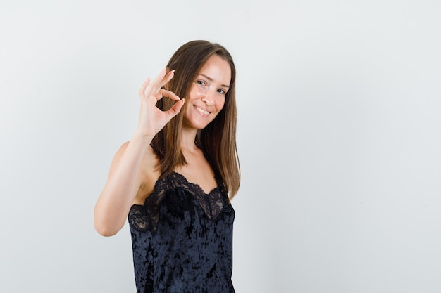 Young female in black singlet showing ok sign and looking cheerful