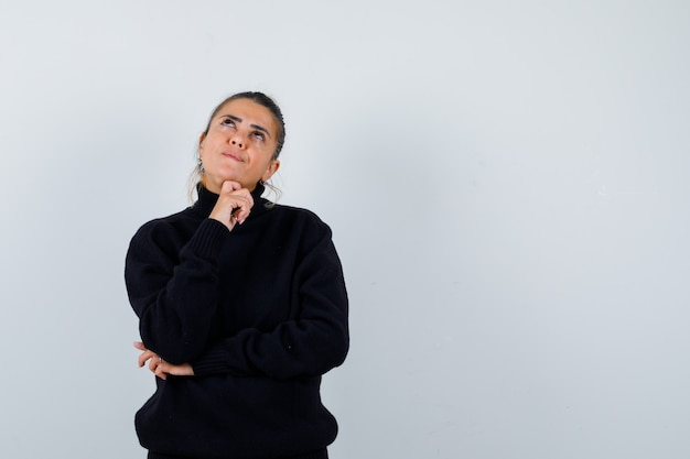 Young female in black turtleneck sweater standing in thinking pose and looking pensive , front view.