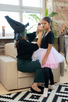 Young female in black witch attire applying makeup on eyes of little girl