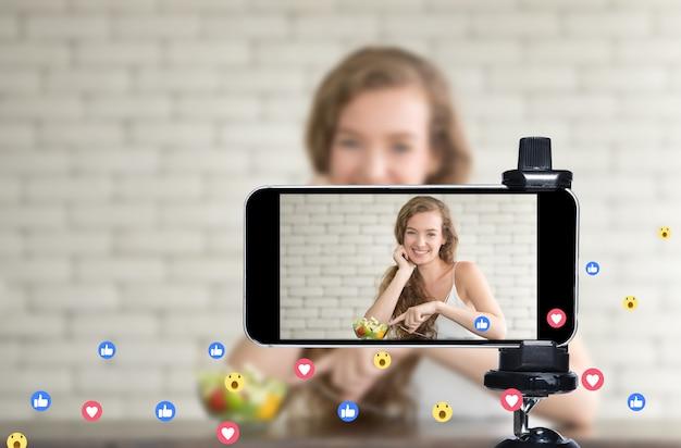 若い女性のブロガーとvlogger、オンラインインフルエンサーがスマートフォンを使用してソーシャルメディアで料理番組をライブストリーミング