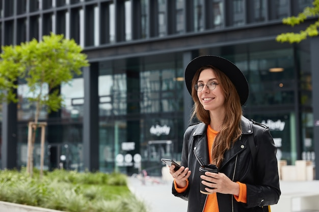 スタイリッシュな服装の若い女性ブロガーは、ウェブサイトを検索するために現代の携帯電話と無料のインターネット接続を使用しています