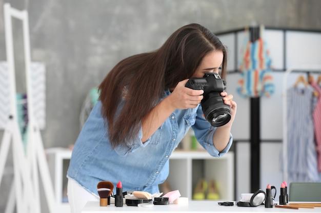 自宅で化粧品の写真を作る若い女性ブロガー