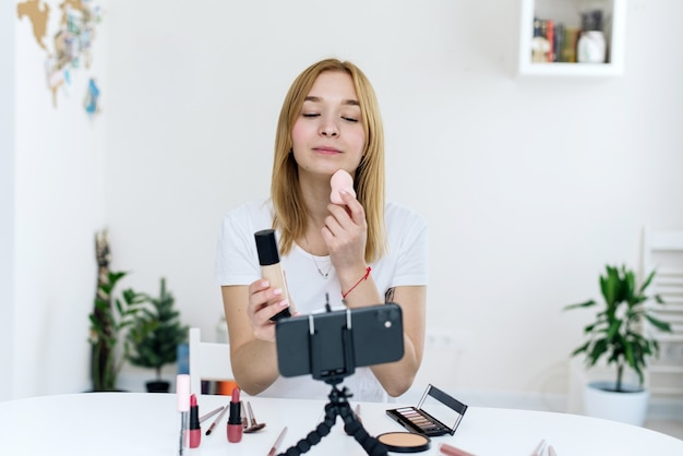 스펀지로 기초를 바르는 방법에 대한 튜토리얼 비디오를 녹화하는 젊은 여성 블로거