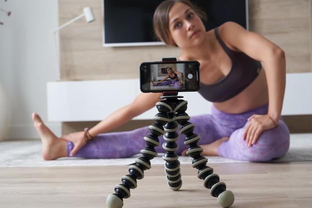 Молодая женщина-блоггер записывает спортивное видео дома, занимаясь йогой в гостиной