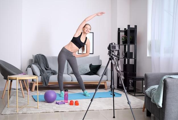 집에서 스포츠 비디오를 기록하는 젊은 여성 블로거