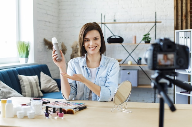 Young female blogger recording a tutorial video for her beauty blog about cosmetics
