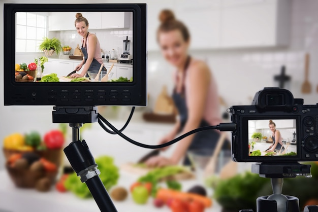 Young female blogger vlogger and online influencer recording video content on healthy food