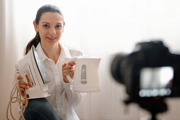 Young female blogger with camera dslr vlogging rewievs household product in bottle modern online work concept